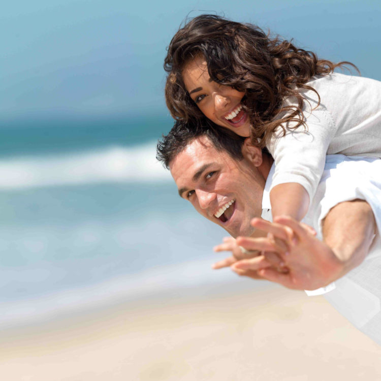 couple smiling and hugging at the beach