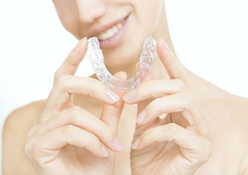girl holding invisalign braces